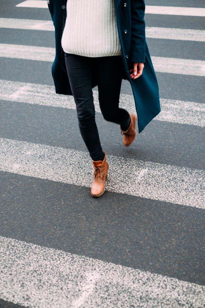 femme portant un jean noir un pull clair des bottines marron et un manteau long sombre